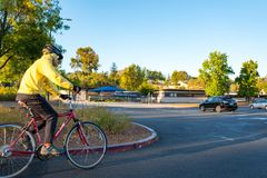 Man Biking. Walnut Creek, California, United States - October 05, 2016:  A man wearing a rain jacket bikes through a park as he commutes to work on his Trek Royalty Free Stock Photos