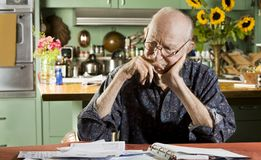 Man with Bills. Elder Man at Home with Bills Royalty Free Stock Photo
