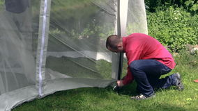 Man bind to arbor bar mosquito screen on windy day, tilt down. Royalty Free Stock Photography