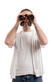 Man With Binoculars. A young man wearing casual clothing is holding a set of binoculars to his eyes, isolated against a white background Royalty Free Stock Photos