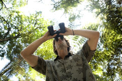 Man with Binoculars. Underview of a man looking through binoculars in the forest Stock Image