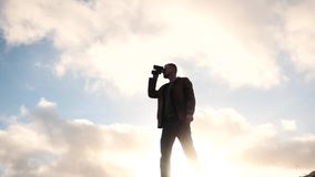Man with binoculars against sun view stock video