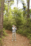 Man with Binoculars Birdwatching on a Forest Trail Royalty Free Stock Photography