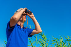 Man with binoculars examines bird Royalty Free Stock Image