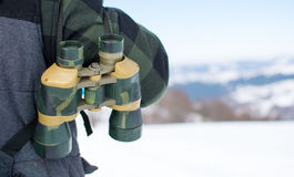 Man with binoculars exploring snowy mountain Royalty Free Stock Images