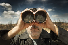 Man with binoculars. In a field stock photo