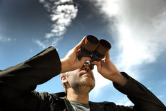 Man with  binoculars. Man with binoculars in a field Royalty Free Stock Images