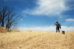 Man with binoculars in a field royalty free stock photography