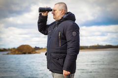 Man with binoculars at the lake. In autumn day Stock Image