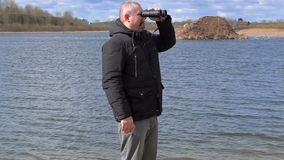 Man with binoculars at the lake stock video footage