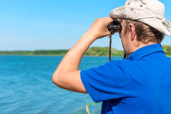 Man with binoculars looks Stock Images