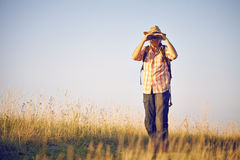 Man with binoculars on meadow. In autumn Royalty Free Stock Images