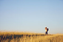 Man with binoculars on meadow. Standing with binoculars on meadow and blue sky Royalty Free Stock Image