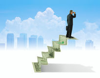 Man with binoculars on money stairs seeking financial success ad Royalty Free Stock Image