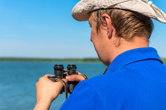 Man with binoculars on the nature Stock Photos