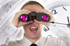 Man with binoculars observing and Clocks with calendar Royalty Free Stock Photography