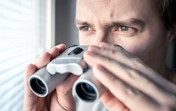 Man with binoculars. Private detective, agent or investigator looking out the window. Man spying or investigating. stock photos