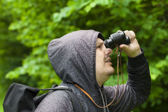 Man with binoculars watching birds in the park Stock Photo