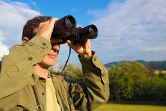 Man with binoculars. Young man with binoculars watching birds in nature, photography Stock Image