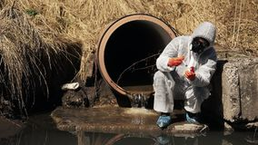 Man in bio-hazard suit and gas mask checks the pollution of the water outside stock video