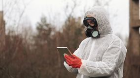 Man in bio-hazard suit and gas mask takes notes in his tablet standing on the polluted land stock video footage