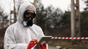 Man in bio-hazard suit and gas mask takes notes in his tablet standing on the polluted land stock footage