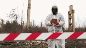 Man in bio-hazard suit and gas mask takes photos on his smartphone stock footage
