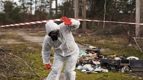 Man in bio-hazard suit and gas masks stands behind the stripe on the territory full of waste stock footage