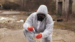 Man in bio-hazard suit and gas masks takes water and ground for the analysis stock footage