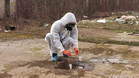 Man in bio-hazard suit and gas masks takes water and ground for the analysis stock video footage