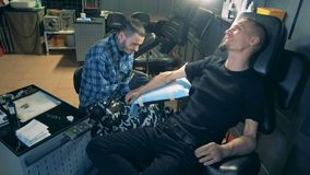Man with bionic hand prosthesis gets a tattoo in a professional salon. 4K stock video
