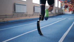 Handicapped person running on a track, back view. stock footage