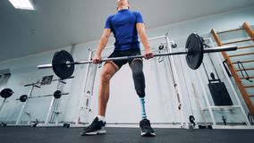 A man with a bionic leg starts lifting heavy weights in a gym. 4K stock video