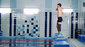 A man with a bionic leg is stretching muscles to jump into the pool stock video