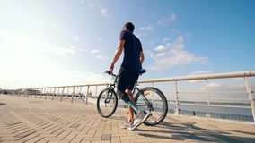 A man with a bionic leg is wheeling a bike along the quay. 4K stock footage