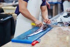 Man bitande atlantiska largeheadhairtails på fiskmarknad Royaltyfri Fotografi