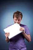 Man bite laptop. Man in lilac shirt bite laptop in studio Stock Image