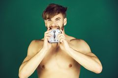 Man biting alarm clock on bearded face. Man or handsome macho biting alarm clock on bearded face with naked torso and strong arms, biceps, triceps on green stock photo