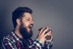Man biting black hamburger. Young man biting fresh tasty black hamburger royalty free stock images