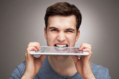 Man biting digital tablet Royalty Free Stock Photos