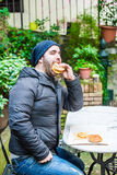 Man biting a hamburger. Man with a jacket and hat biting a hamburger - green background royalty free stock photography