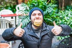 Man biting a hamburger and making an approving sign / thumbs up Royalty Free Stock Image