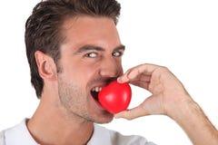 Man biting heart-shaped object Stock Image