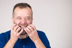 Man biting his nails. Stress, anxiety, emotions and problems concept. Scared, stressed man biting his nails royalty free stock photos