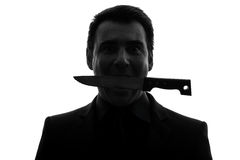 Man biting knife silhouette Royalty Free Stock Photography