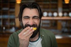 Man biting into lemon wedge after having tequila shot Royalty Free Stock Photo