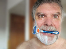 Man biting razor Stock Photo