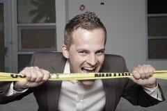 Man biting through the tape Royalty Free Stock Photos