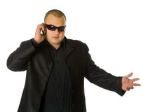 Man in black. Suit in sun glasses talking on the mobile phone. Isolated on white background stock photo
