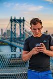 Man in Black Adidas Crew Neck T Shirt Holding Silver Iphone Near Bridge during Daytime Stock Photo
